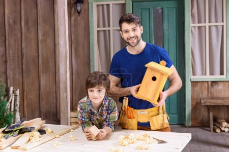 Father and son making birdhouses
