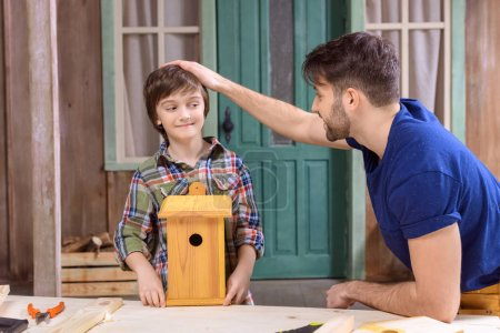 Father and son making birdhouse