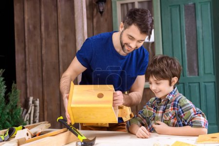 Photo for Happy father and son making wooden birdhouse together in workshop - Royalty Free Image