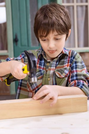 Boy hammering nail