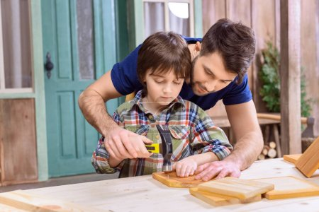 Photo for Smiling father teaching concentrated son to hammering nail in wooden plank - Royalty Free Image