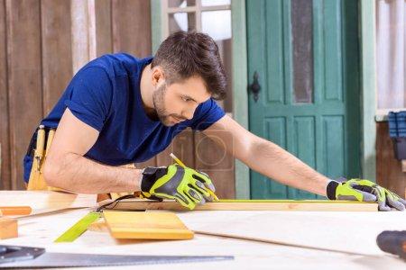 Foto de Vista lateral del carpintero concentrado en guantes de protección medidas de tabla de madera - Imagen libre de derechos