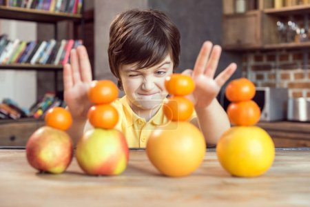 Photo for Cute little boy playing with fresh fruits on wooden table - Royalty Free Image