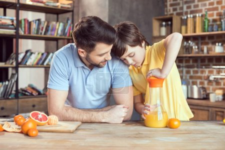 Photo for Father and son squeezing fresh orange juice at kitchen table - Royalty Free Image