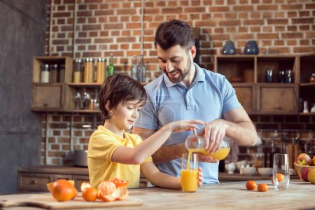 Photo for Happy father and son pouring fresh juice in glass - Royalty Free Image