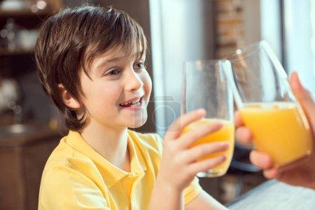 Photo pour Souriant petit garçon et père cliquetis verres avec du jus frais - image libre de droit