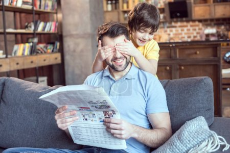 Photo for Boy closing father's eyes while reading newspaper at home - Royalty Free Image