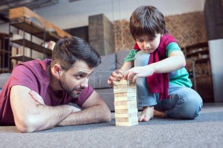 Photo pour Concentré père et fils jouer jenga jeu à la maison - image libre de droit