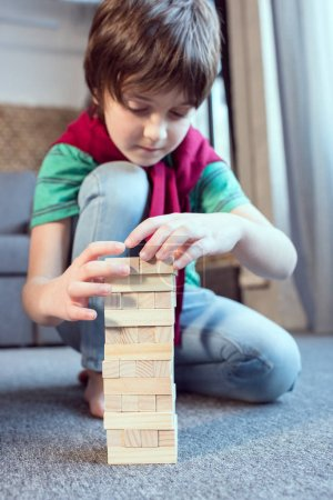 Photo for Concentrated boy playing jenga game at home - Royalty Free Image
