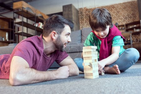 Photo for Low angle view of father looking at son playing jenga game - Royalty Free Image