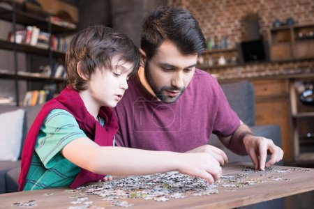 father and son palying with puzzles