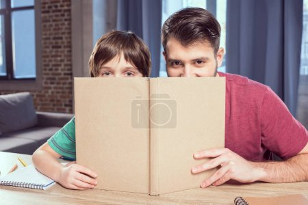 Photo for Father and son looking out of book at home - Royalty Free Image