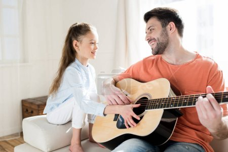 Father and daughter playing guitar