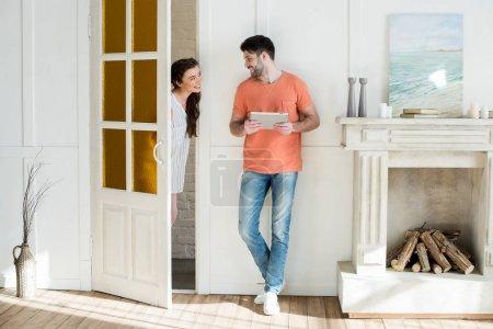 Photo pour Heureuse jeune femme et homme avec tablette numérique en regardant l'autre à la maison - image libre de droit