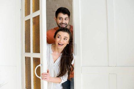 Photo pour Happy surpris debout jeune couple dans la porte - image libre de droit