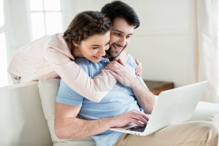 Photo for Portrait of smiling woman hugging man while using laptop - Royalty Free Image