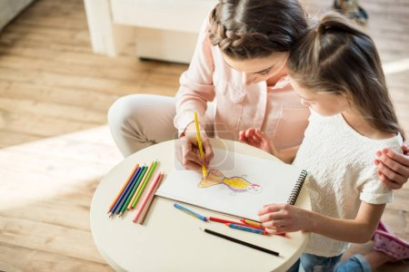 Photo for High angle view of mother and daughter drawing picture together - Royalty Free Image