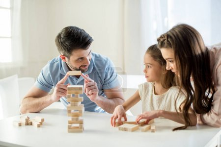 Photo for Portrait of concentrated parents playing jenga game with daughter - Royalty Free Image