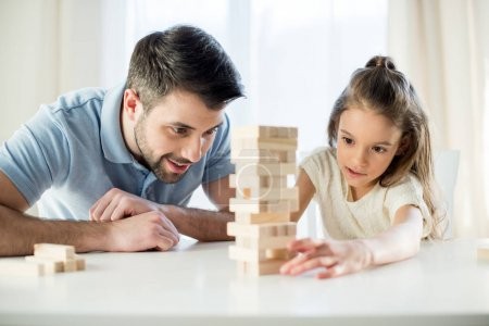 Photo for Portrait of focused daughter playing jenga game with father at home - Royalty Free Image
