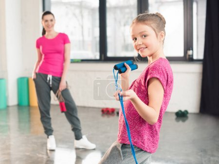 Photo for Mother looking at cute little daughter holding skipping rope and smiling at camera - Royalty Free Image