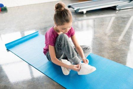 Girl tying shoelace