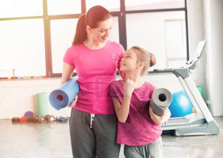 Photo for Mother and daughter in pink shirts holding yoga mats in gym - Royalty Free Image