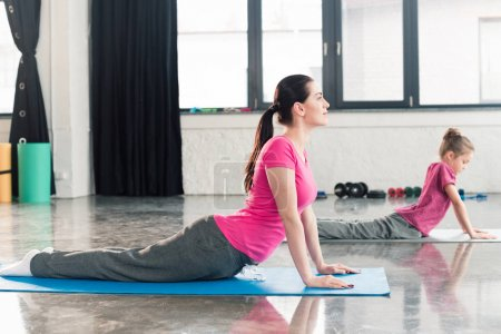 Photo for Mother and daughter in pink shirts practicing yoga in Cobra Pose in gym - Royalty Free Image