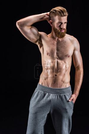 Photo pour Torse nu bodybuilder barbu posant isolé sur noir en studio - image libre de droit