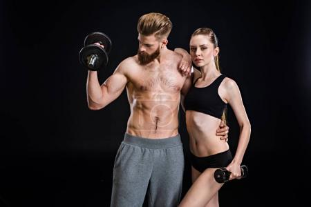 Sportswoman and sportsman training with dumbbells