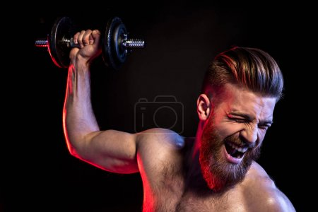 Photo for Handsome bodybuilder training with dumbbell isolated on black with dramatic lighting - Royalty Free Image