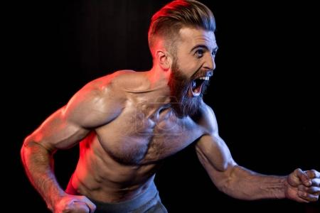 Photo for Handsome bodybuilder gesturing and yelling isolated on black with dramatic lighting - Royalty Free Image