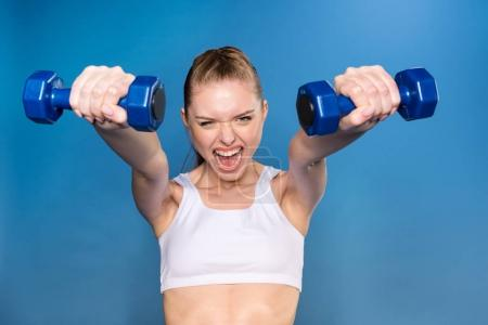 Photo for Aggressive young sportswoman training with dumbbells isolated on blue in studio - Royalty Free Image