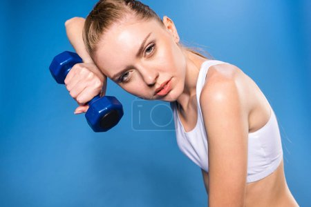 Sportswoman training with dumbbell