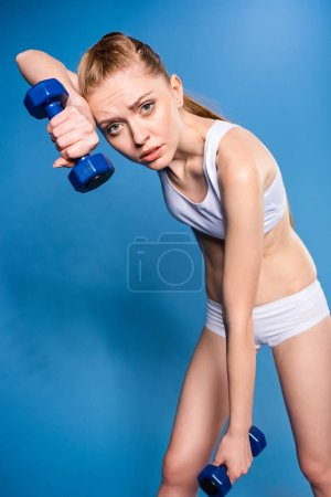 Sportswoman training with dumbbells