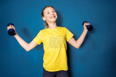preteen girl training with dumbbells