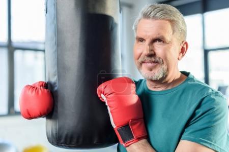 Photo pour Sportif senior dans les gants de boxe rouges avec sac de boxe en cours de conditionnement physique - image libre de droit