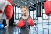 preteen girl boxing with trainer.
