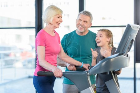 senior couple and girl on treadmill