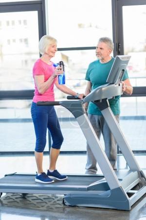senior couple training on treadmill