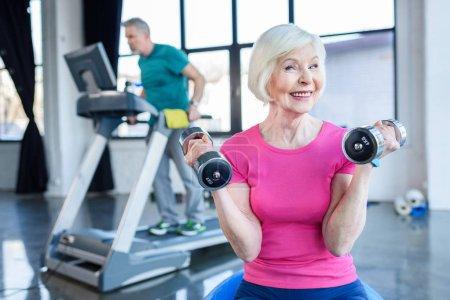 Photo pour Sportive Senior assis sur ballon de fitness avec haltères, sportif sur tapis roulant derrière en cours de conditionnement physique senior - image libre de droit