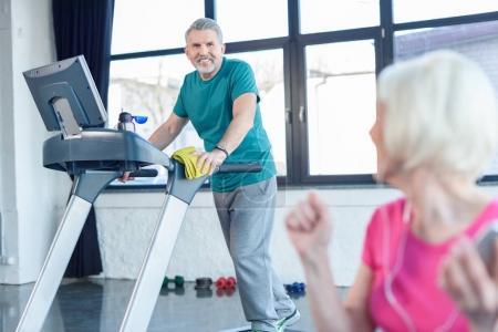 Photo pour Senior sportif entraînement sur tapis roulant, sportive senior sur le premier plan en cours de conditionnement physique senior - image libre de droit