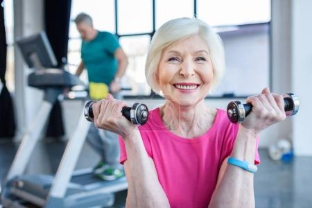 senior sportswoman with dumbbells