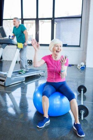 Photo pour Sportive Senior assis sur boule de remise en forme avec le smartphone, sportif sur tapis roulant derrière en cours de conditionnement physique senior - image libre de droit