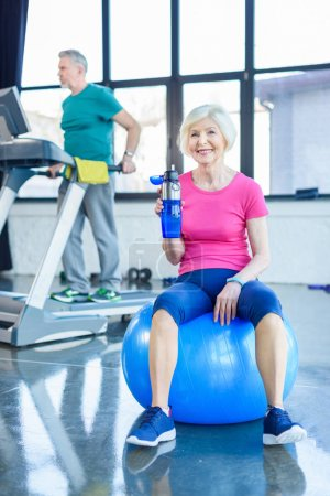 Photo for Smiling senior woman sitting on fitness ball and drinking water in fitness class - Royalty Free Image