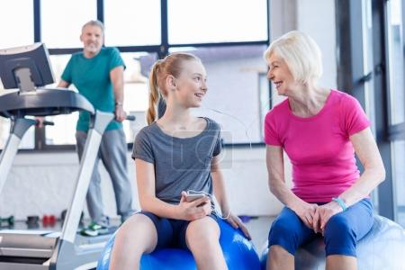 Senior woman with girl in gym
