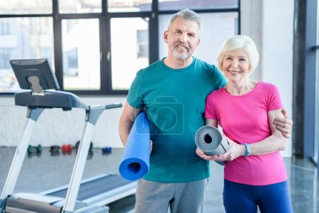 Photo for Happy fitness couple holding yoga mats and smiling at camera in gym - Royalty Free Image