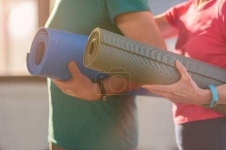 Photo pour Gros plan partiel du couple de remise en forme maintenant des tapis d'yoga en gym - image libre de droit