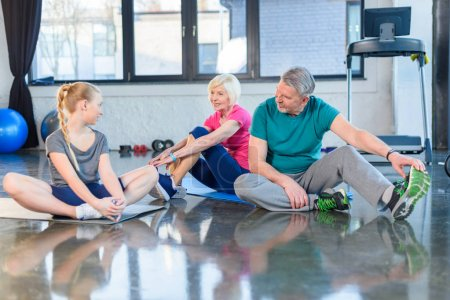 Photo for Smiling senior couple and girl sitting on yoga mats in fitness class - Royalty Free Image
