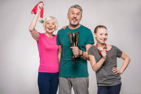 Photo for Cheerful old couple and girl holding sport trophy and medals isolated on grey - Royalty Free Image