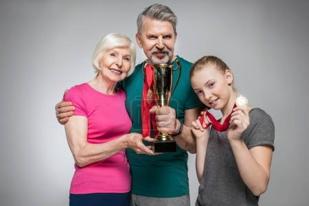 Photo for Happy old couple and girl holding sport trophy and medals isolated on grey - Royalty Free Image